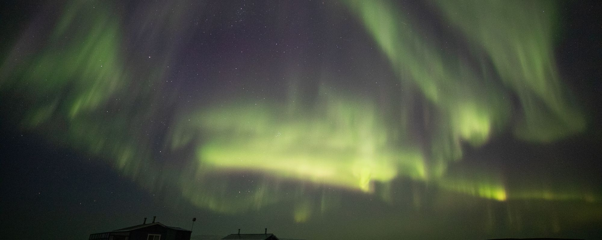 Northern Lights dance over guest cabins at Peterson's Point Lake Lodge