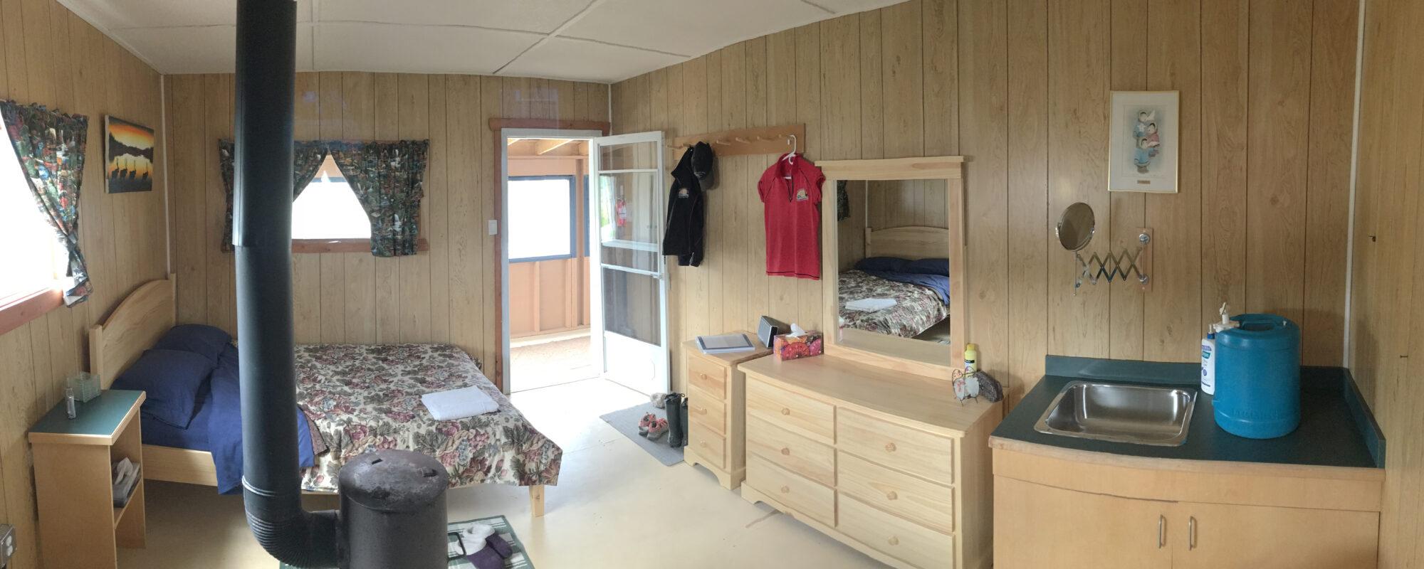 Inside Cabin Suite Queen bed and dresser, mirror and vanity