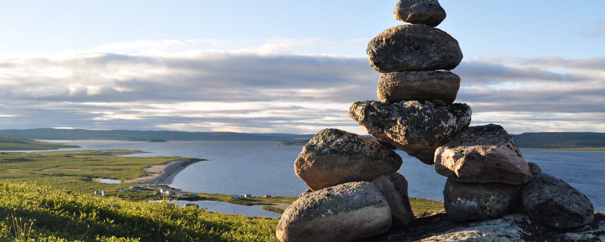 View from ridge overlooking Point Lake with view of lodge and inukshuk in foreground
