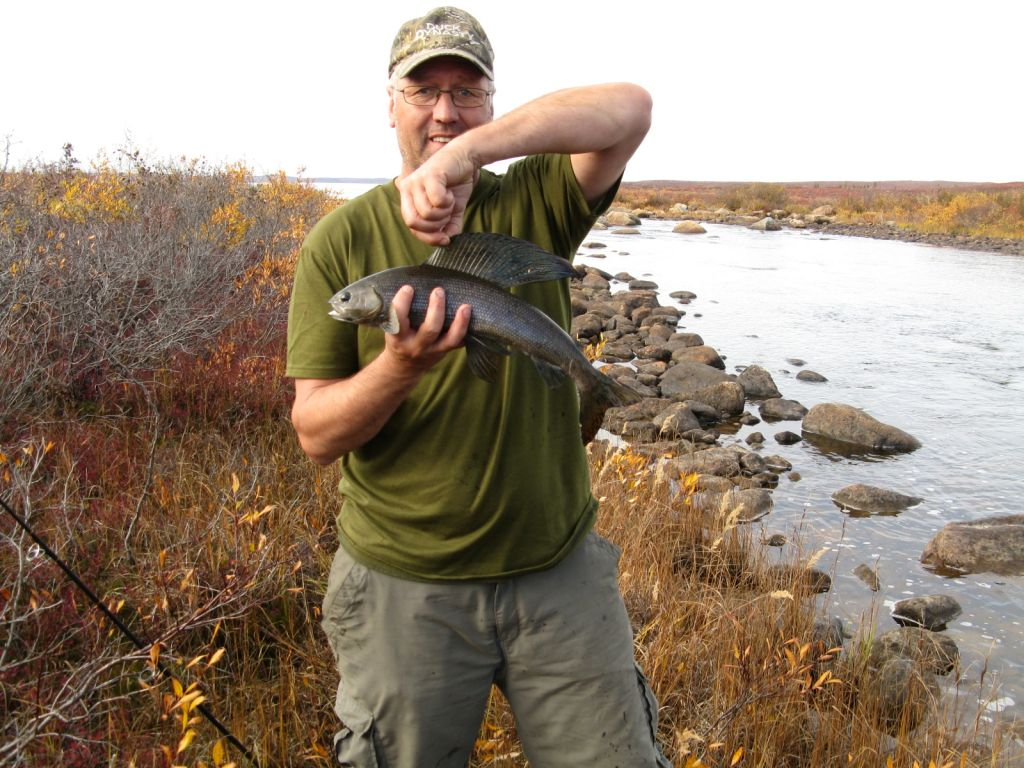 A man smiling, holding the dorsal fin of an Arctic Grayling on the shore of the Itchen River