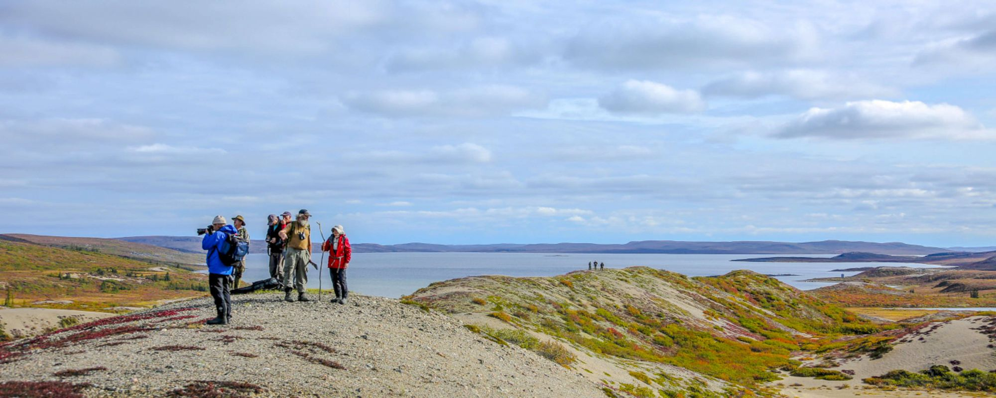 People on sand esker taking photos and over looking Point Lake and the barrens