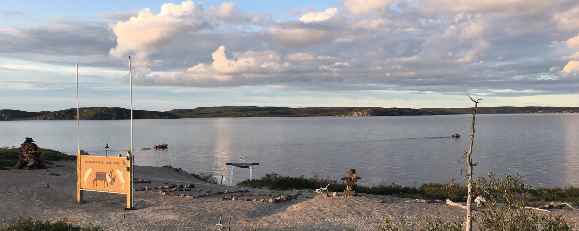 Two boats heading out on a summer evening on Point Lake to go fishing for trophy lake trout in the Northwest Territories Canada