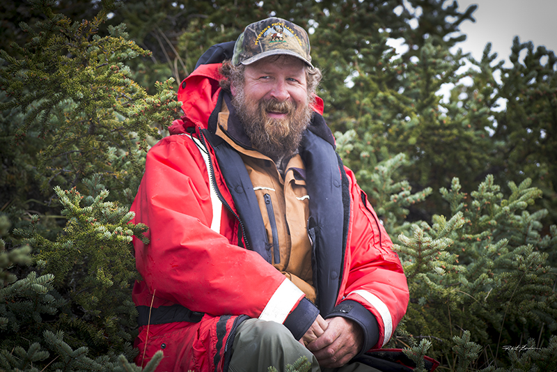 A bearded man wearing a Mustang Life jacket with stunted spruce tree behind him. He has a big smile