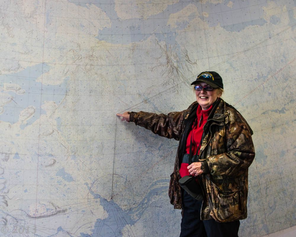 Woman pointing at large map of the Northwest Territories to specific location, Point Lake.