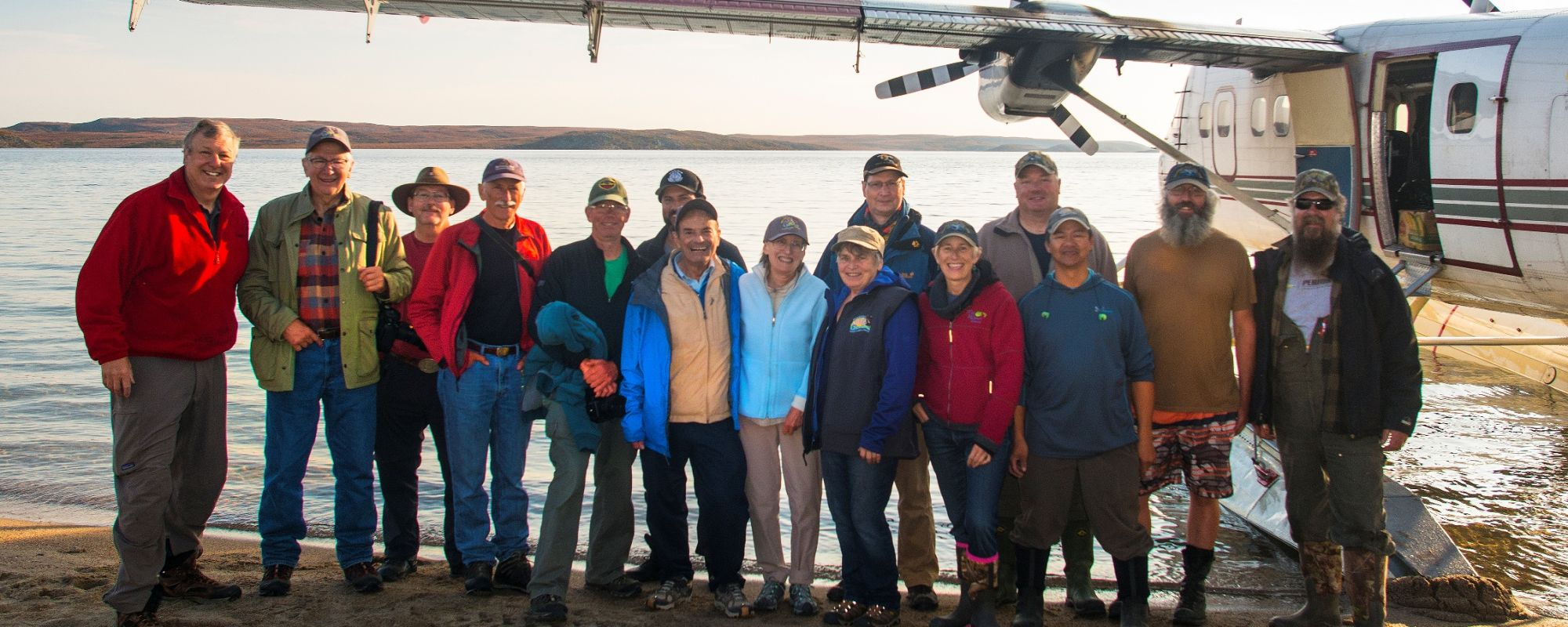 Group of People Standing on beach near float plane smiling