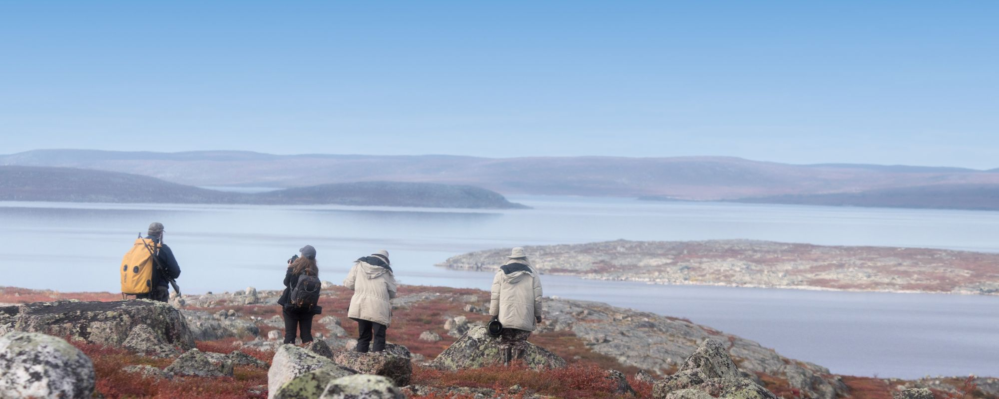Group of people walking on hill top scenic view of a lake and barrenlands