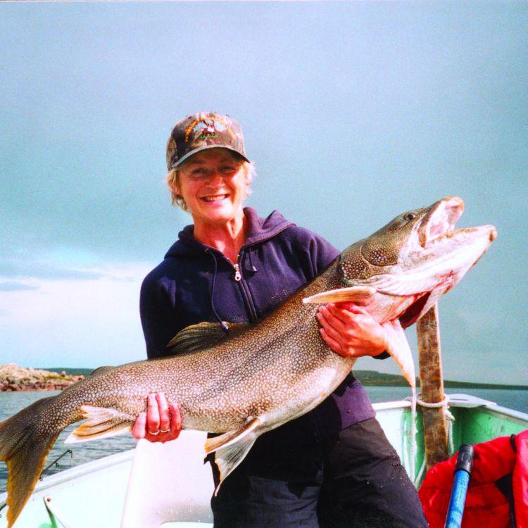 Female Angler holding monster lake trout